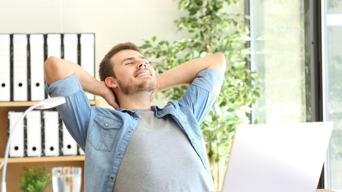 Relaxed entrepreneur sitting on a chair with arms in the head sitting on a chair at office