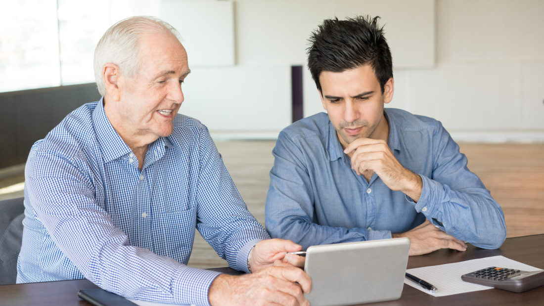 Friendly senior man showing something to young colleague at tablet screen. Mentor training young employee. Business meeting and mentoring concept