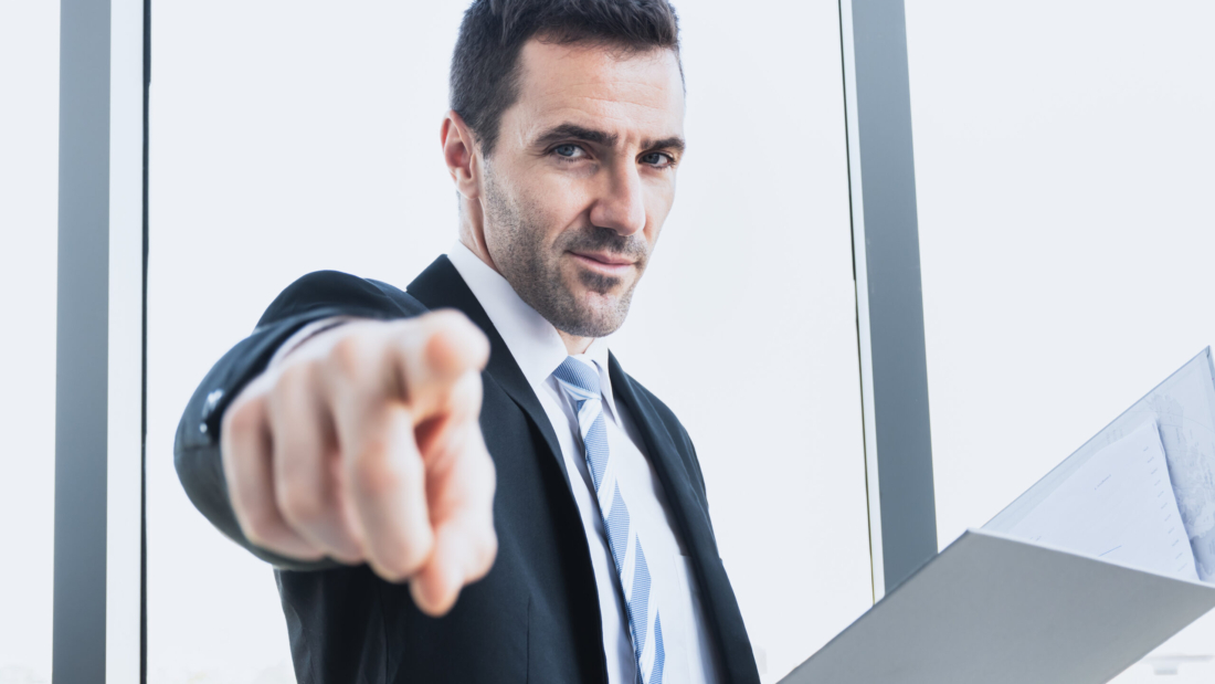 A businessman is pointing the finger to command work with an office worker. The boss is pointing a finger into an employee in the company. The businessman points the finger at you.